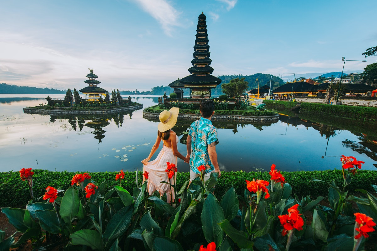 Couple spending time at the ulun datu bratan temple in Bali. Concept about exotic lifestyle wanderlu...