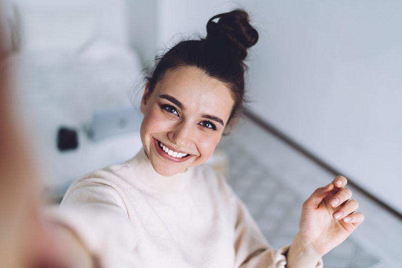 Pretty young female with big smile standing at bedroom after work with laptop and having fun taking ...