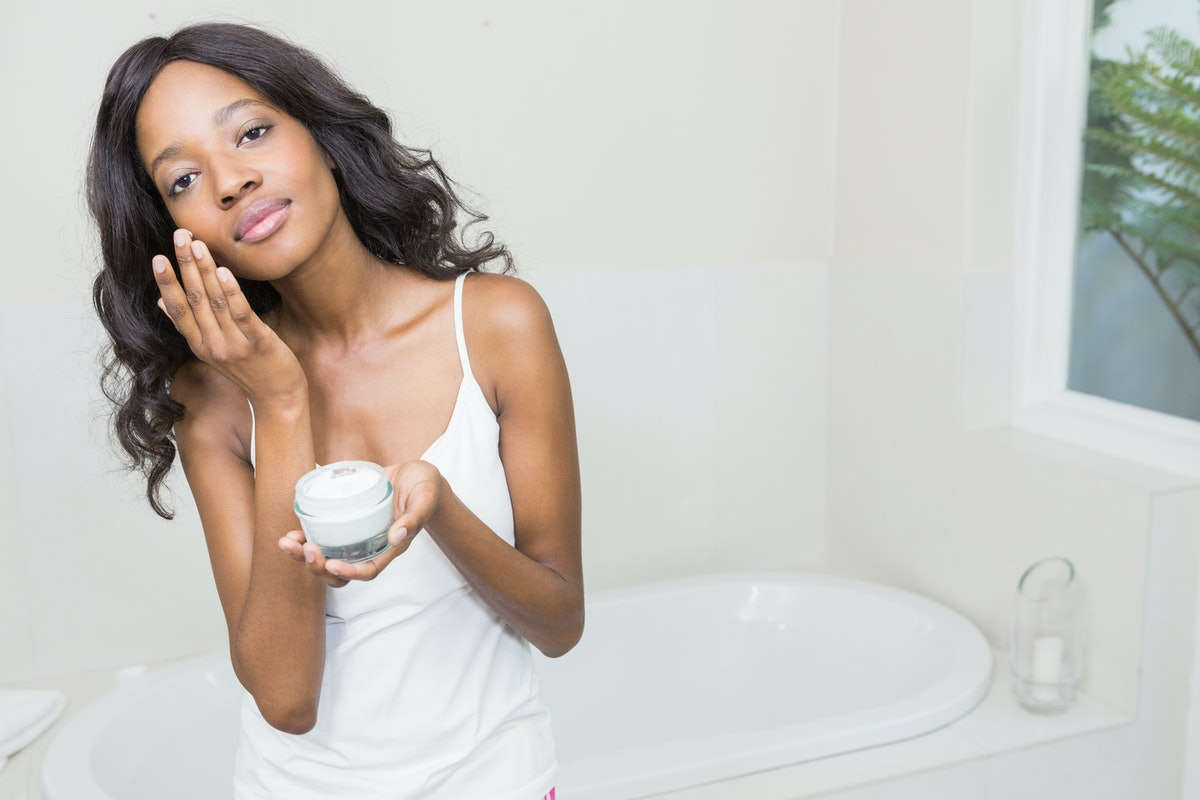 Young woman applying moisturizer to her skin
