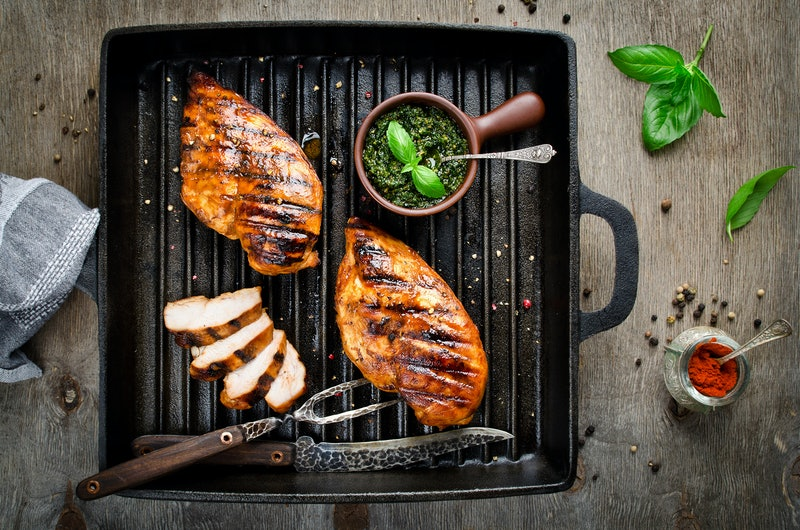 Chicken fillet in the grill pan. Grilled meat with pesto sauce