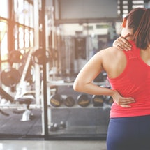 A person wearing a red workout shirt faces away from the camera, rubbing at a sore spot in their neck at the gym. Gyms are not often welcoming to people with chronic pain.