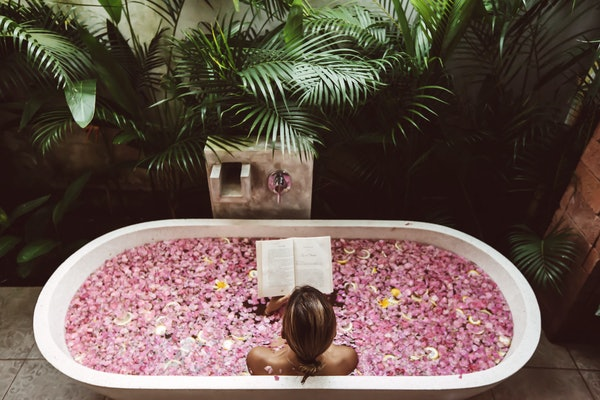 A young woman reads a book while soaking in a flower bath in the jungle.