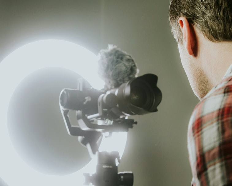 A man streaming, video recording with a mirror less camer and ring light.