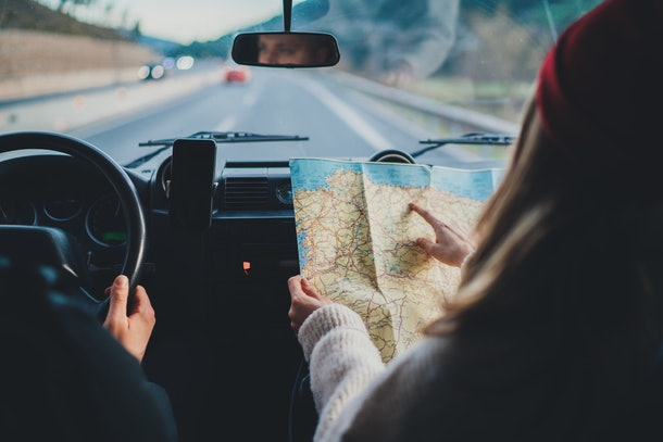 Happy couple traveling by authentic car in Europe, hipster girl holding touristic map planning route in mountains, lifestyle roadtrip travel concept