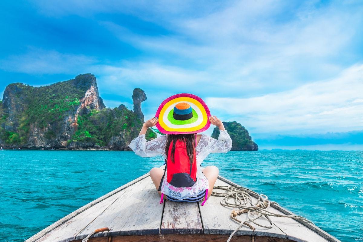 Summer lifestyle traveler woman in bikini and big hat joy relaxing on boat, Kai island, Andaman sea,...