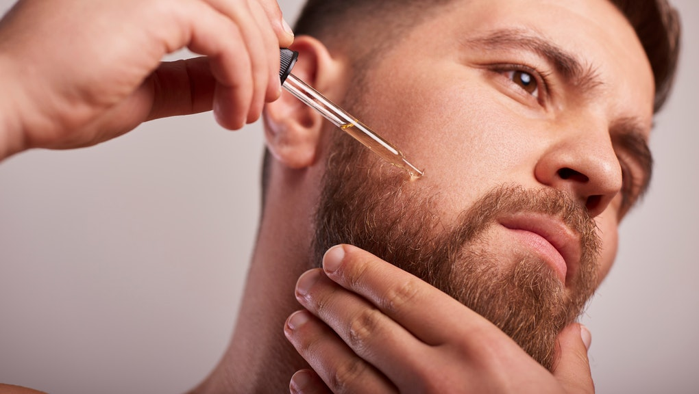 Close-up image of handsome man holding pipette with oil for beard