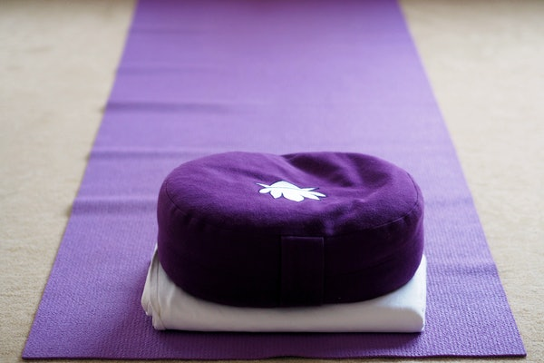 Purple coloured yoga mat and yoga cushion in a yoga room.
