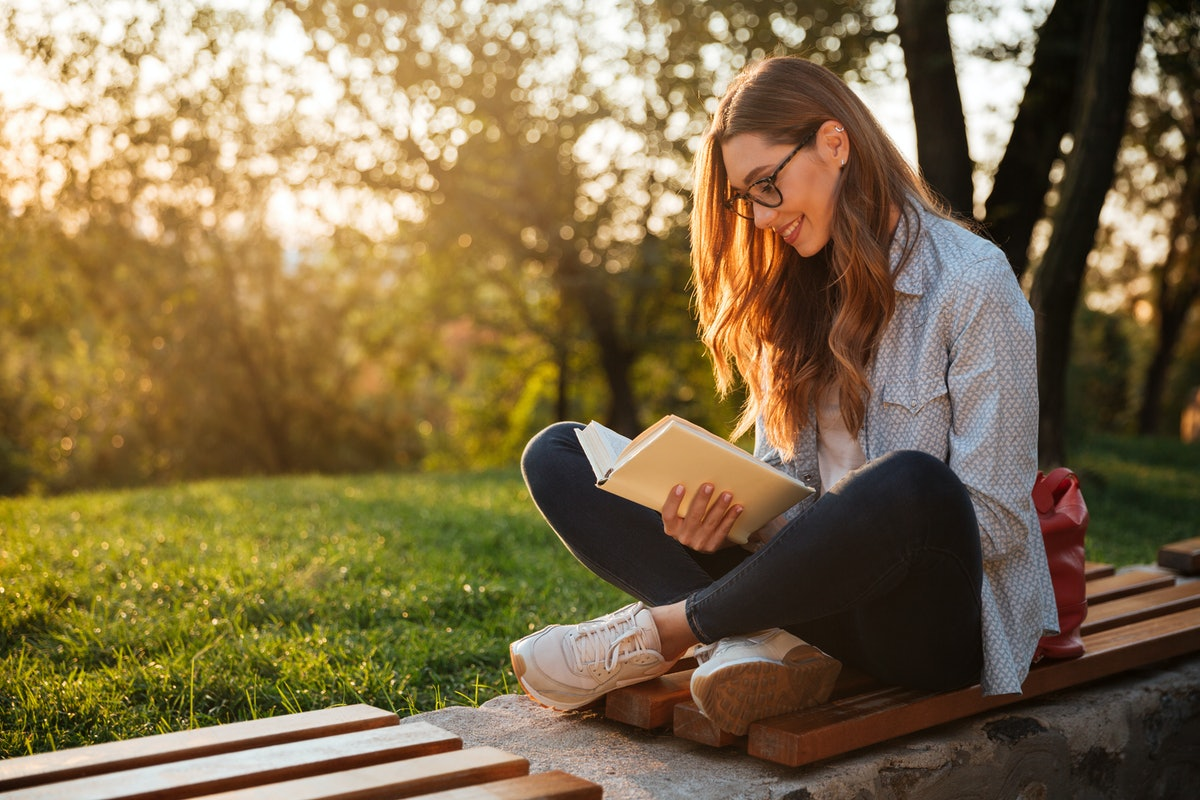 Side view of pleased brunette woman in eyeglasses sitting on bench and reading book in park