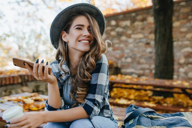 Pretty laughing girl with smartphone has a good time in autumn weekend. Outdoor portrait of lovable ...