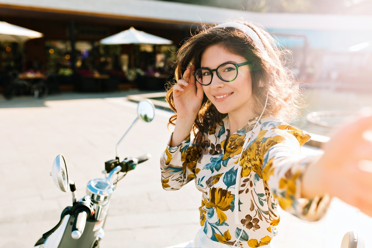 Cute girl with pretty shy smile making selfie, chilling after bike ride around city in weekend. Outdoor portrait of attractive young woman in glasses and headphones cover eyes from sunshine.