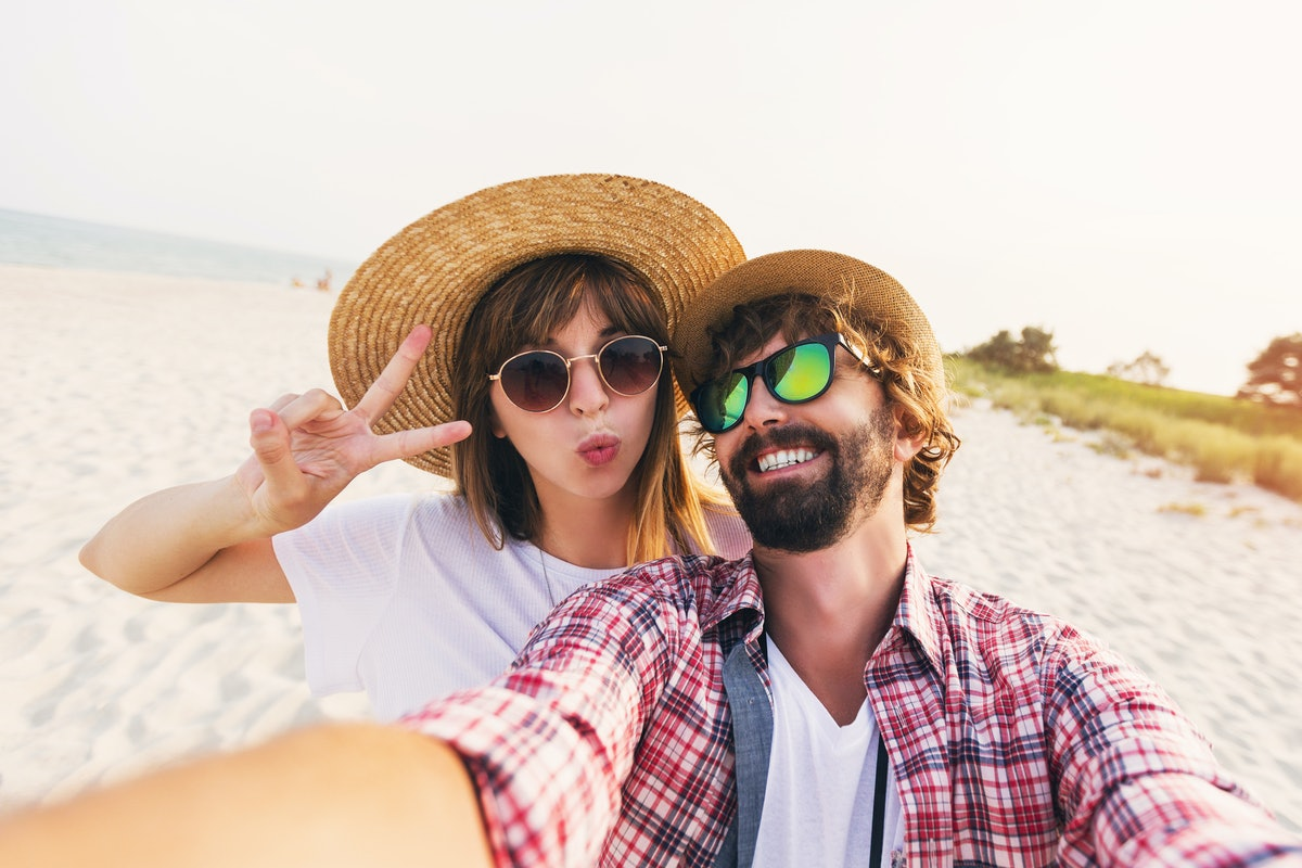 Happy young  couple in love making a selfie on phone at the beach on a sunny summer day. Pretty girl...