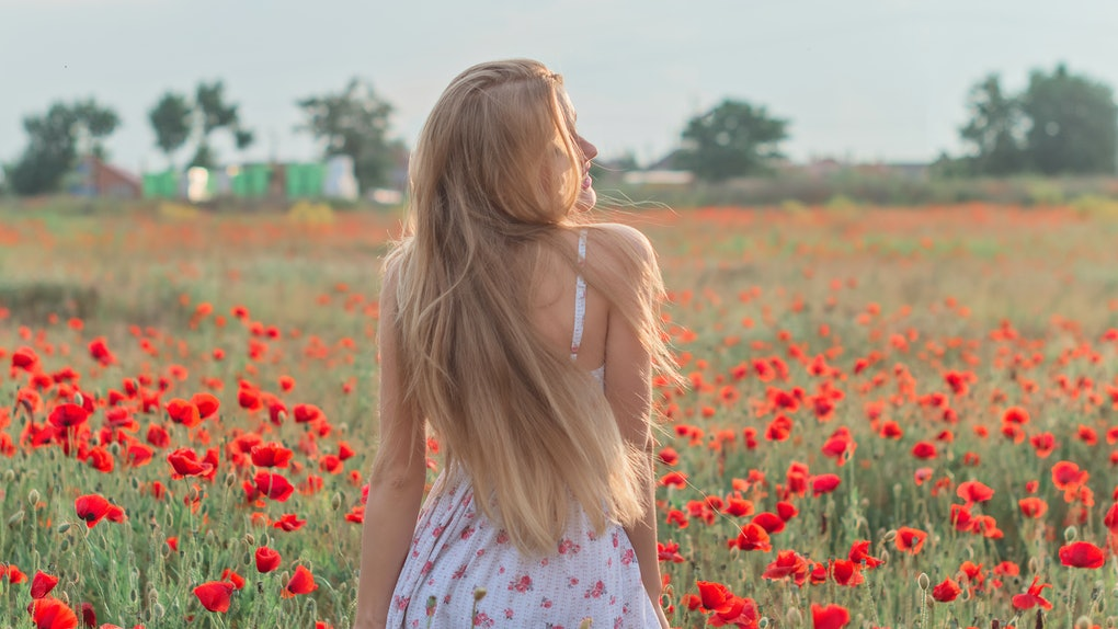 A woman with long blonde hair wearing a white sundress with flowers on it twirls in a flower field with red tulips.