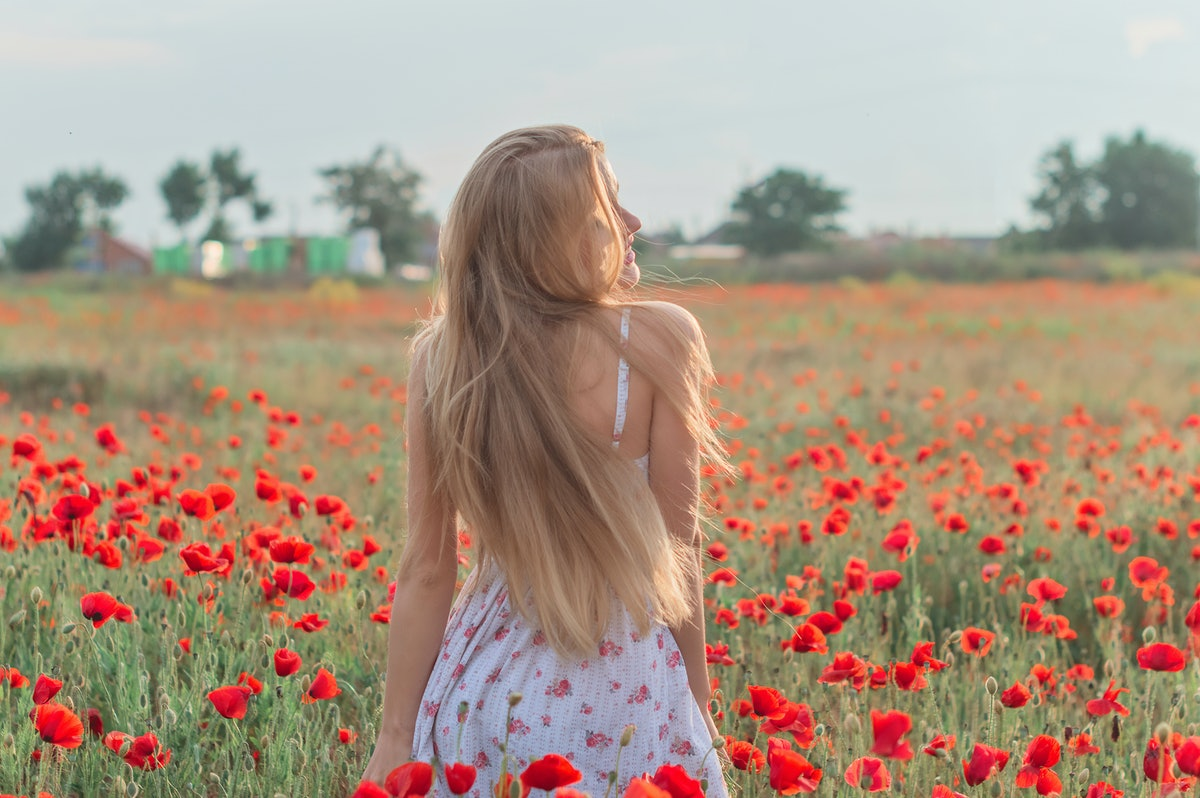 A woman with long blonde hair wearing a white sundress with flowers on it twirls in a flower field w...