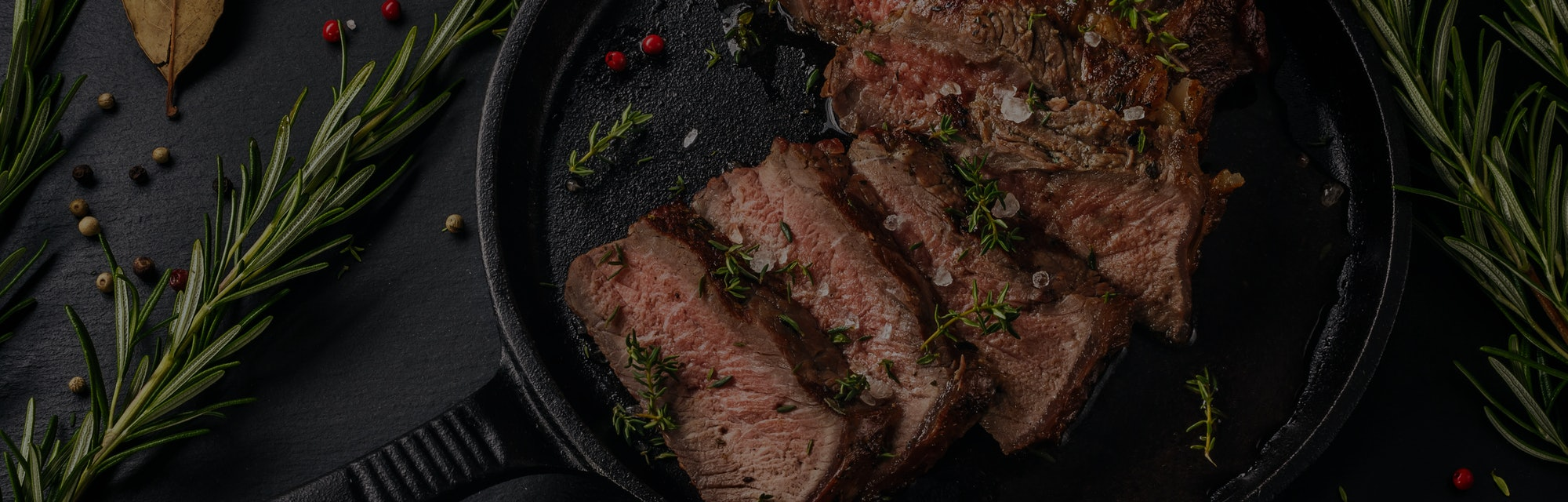 Tender sliced sous-vide beef steak from in a cast iron pan on slate board. Top view