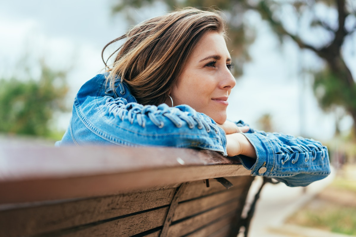Young woman sitting on a bench outdoors in a park leaning on the back staring into the distance daydreaming