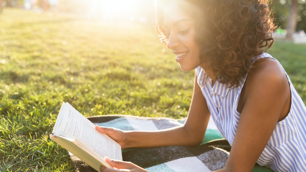 Happy african girl laying on a grass at the park, reading book