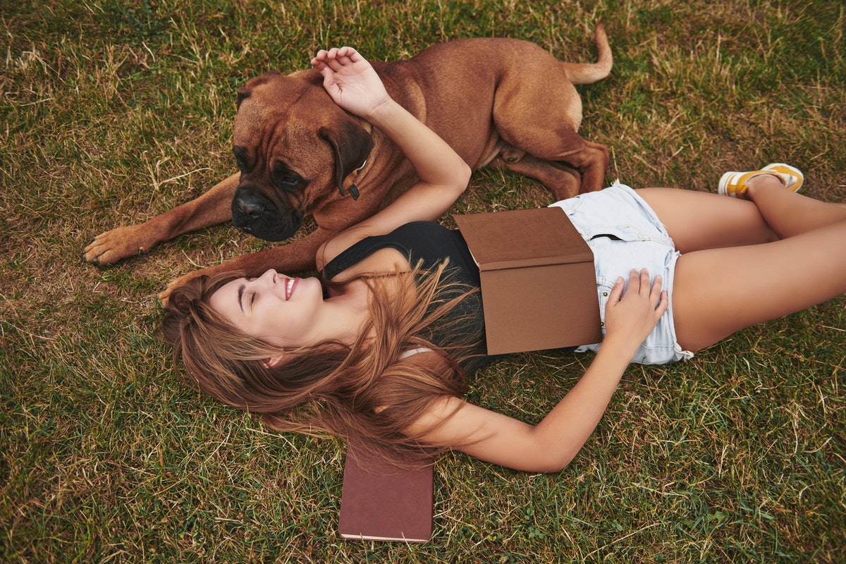 Calm and peace. Lying on the ground. Woman have a walk with her dog outdoors in the park. Having good time.