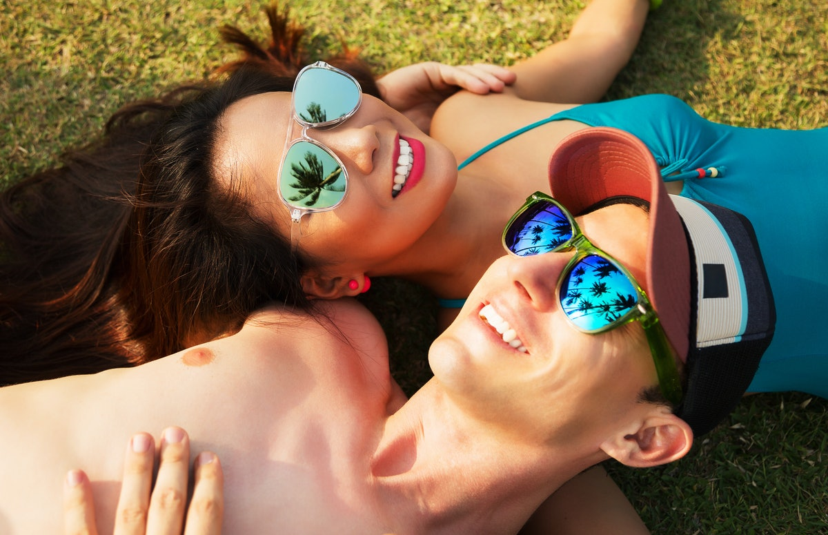 Outdoors lifestyle portrait of happy couple in love. Smiling, lying on the grass and looking at the sky. Wearing bright bikini, cap and stylish sunglasses. In sunglasses reflected palm trees