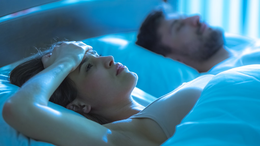 The woman with a headache lay near the man in the bed. night time