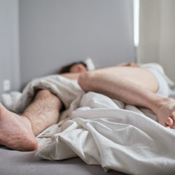 Photo of legs of gay couple under a blanket.