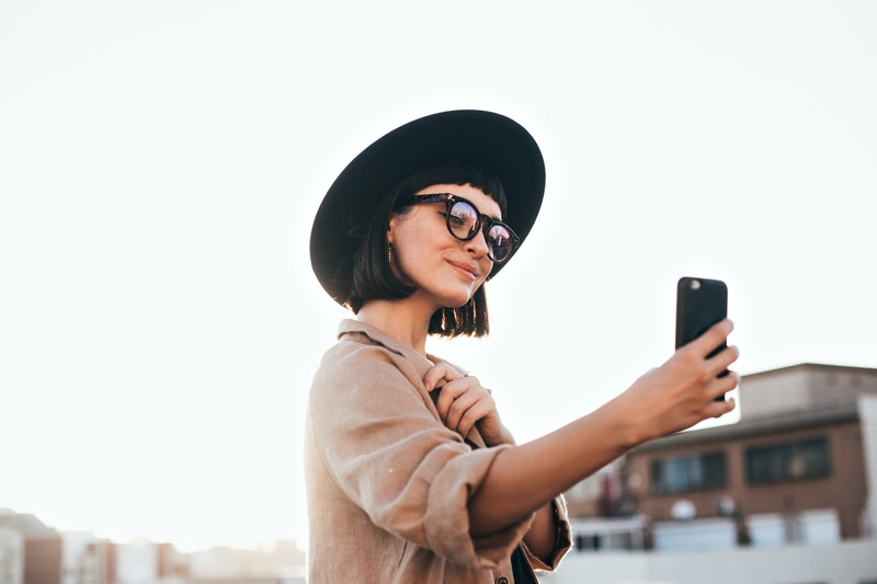 Cute and pretty fashion trendy and hipster millennial woman or girl makes selfie on smartphone camera to share on internet social media channels, self absorbed new generation of young people