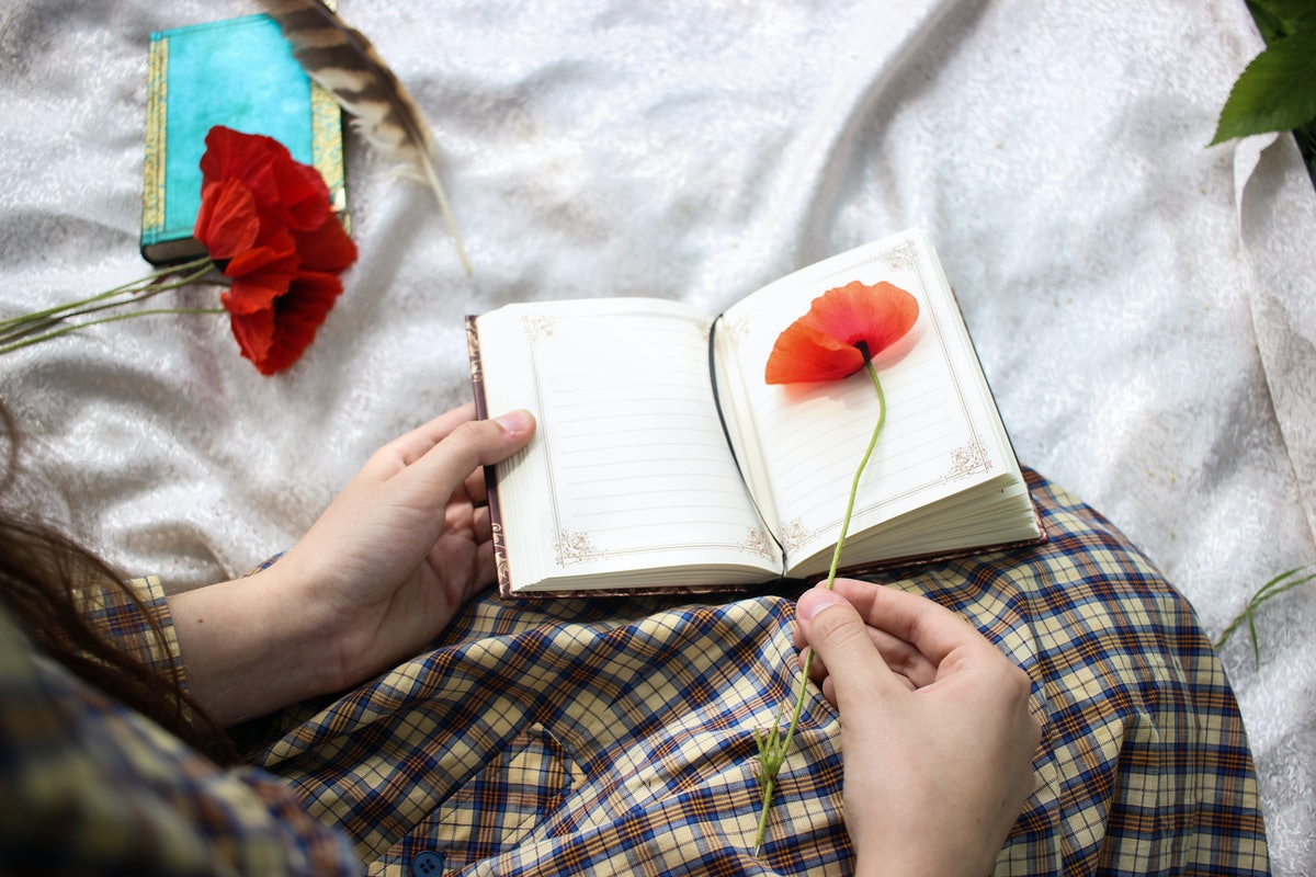 A woman in a retro plaid dress sits on her bed and presses flowers in a vintage book.