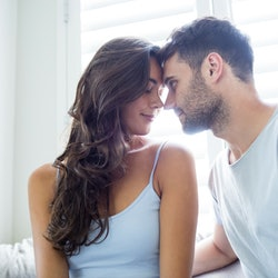 Young couple romancing in bedroom at home