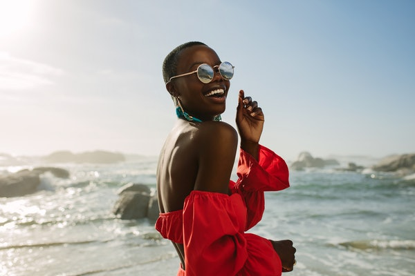 A happy woman in a red off-the-shoulder top, blue dangly earrings, and round sunglasses smiles near the water at the beach.