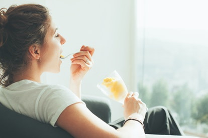 Young woman in white t-shirt sitting near big bright window eating ice cream
