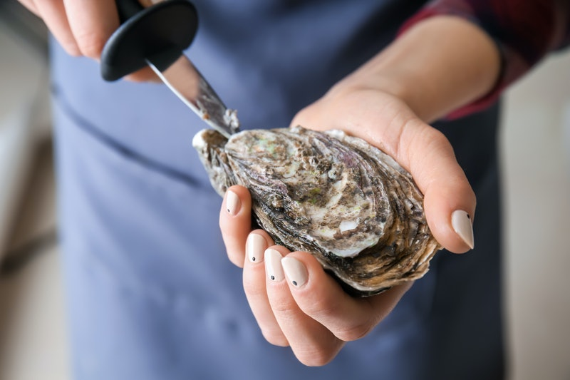 Woman opening raw oyster with knife, closeup