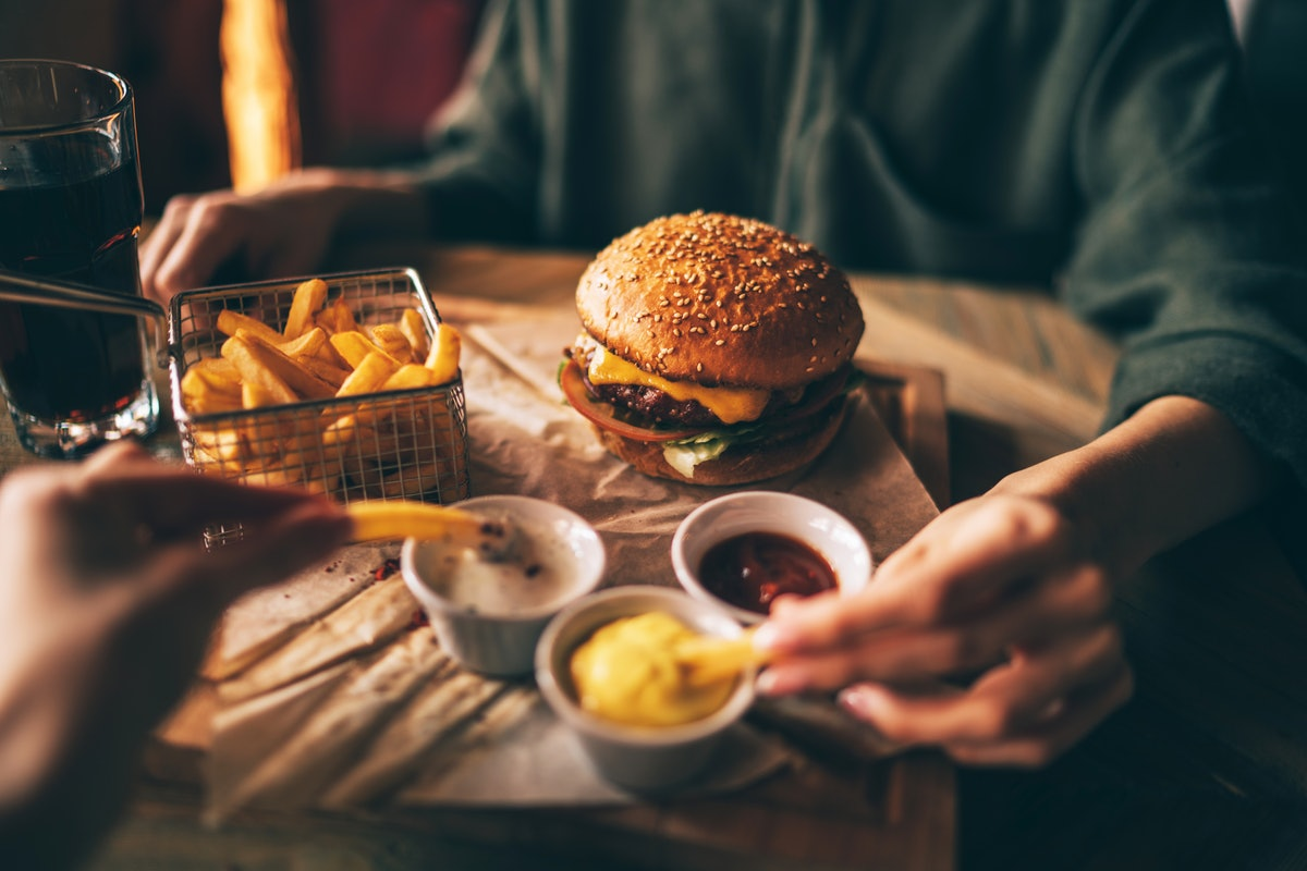 Group of friends eating at fast food. Friends are eating burgers while spending time together in cafe.Tasty grilled beef burger with lettuce and mayonnaise served on pieces of brown paper.