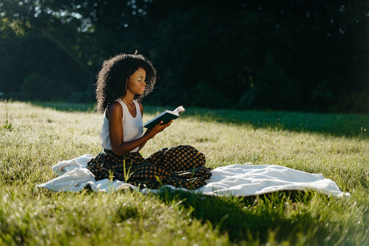 Charming african girl with natural make-up and curly hair is relaxing with the book during the picnic on the sunny meadow.