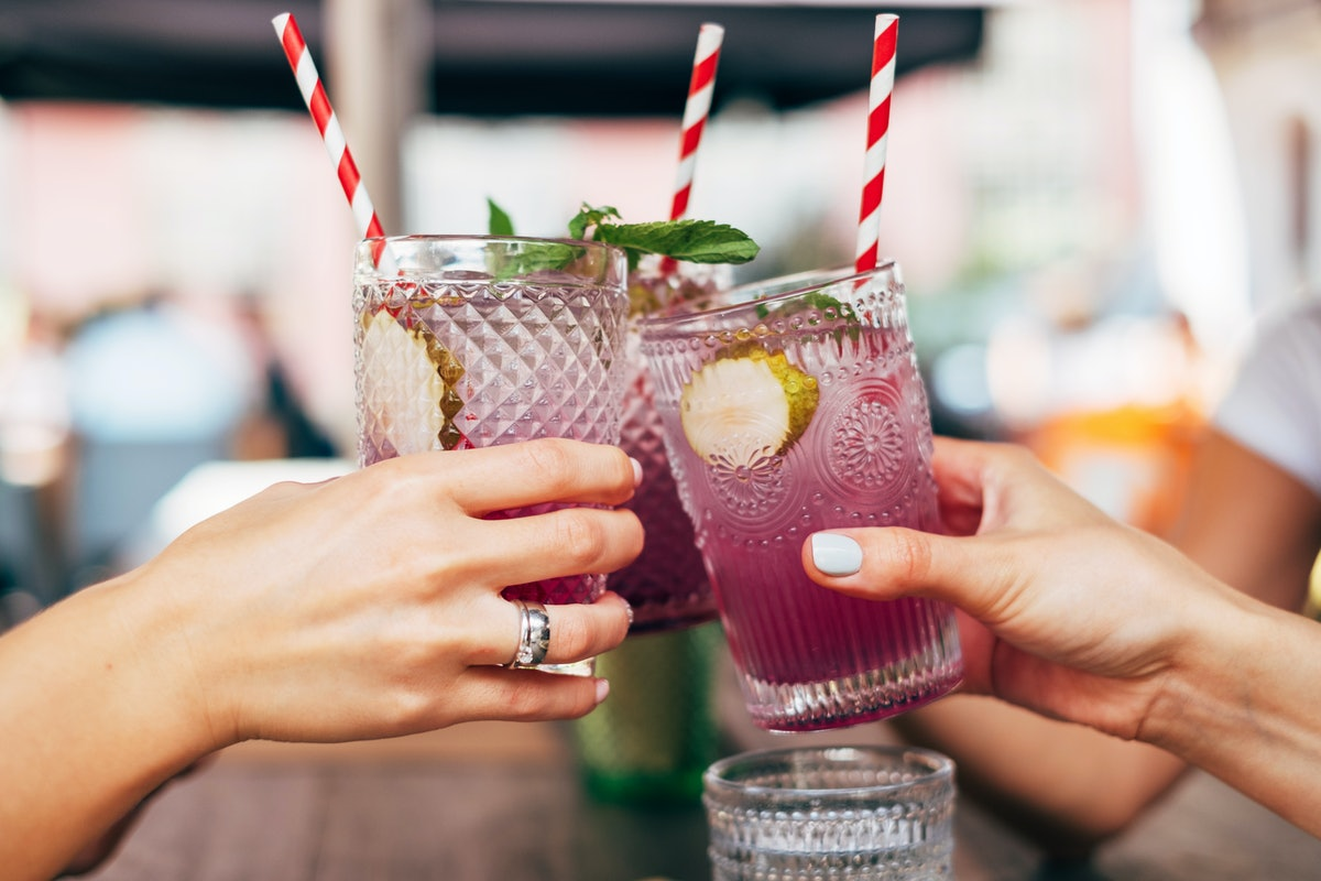 A group of friends holding lavender cocktails toast before drinking.