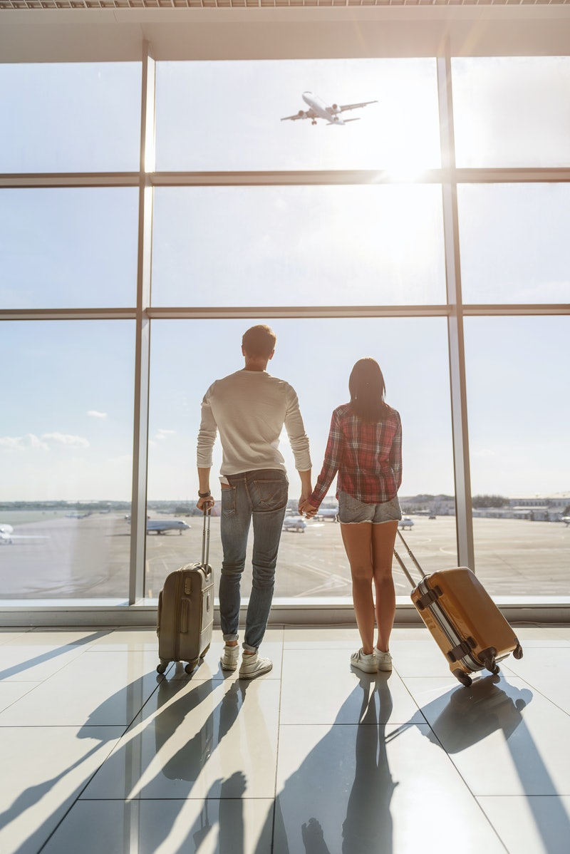 Dreamful loving couple is ready for travel. They are standing near window at airport and looking at flying plane. Lovers are holding hands