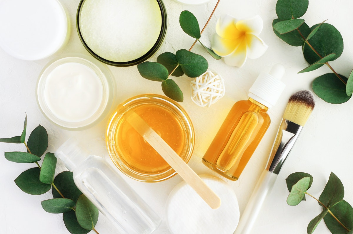Natural cosmetics ingredients for skincare, body and hair care. Golden honey in jar and green herbal...