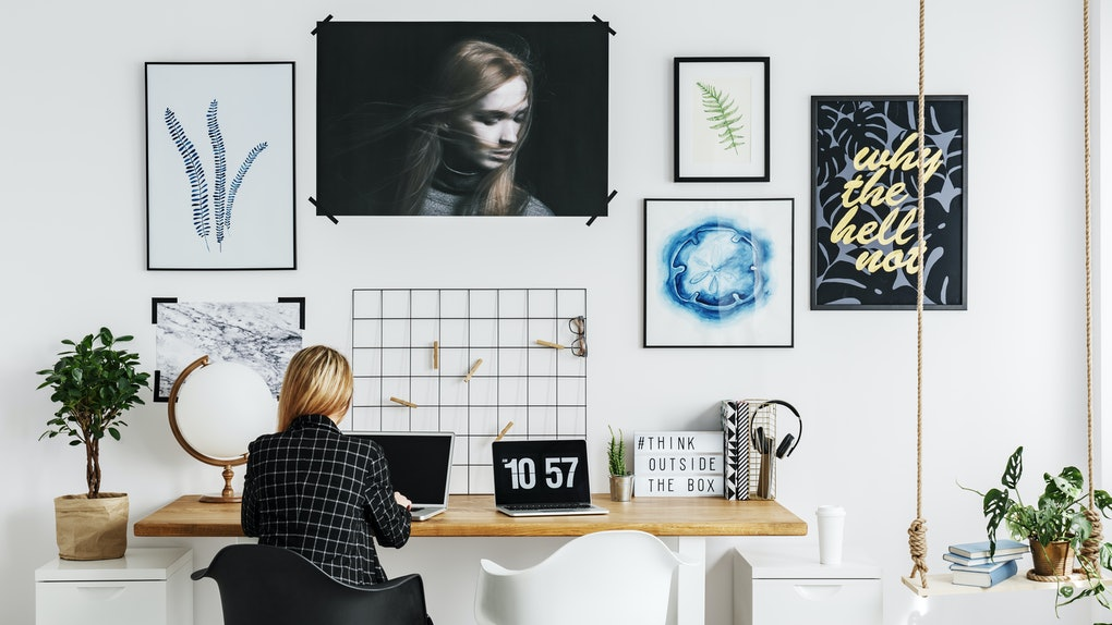 A blonde woman with a black and white flannel sits at a trendy desk in her home.