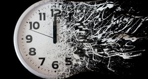 Time is running out concept shows clock that is dissolving away into little particles. Black and white wall clock