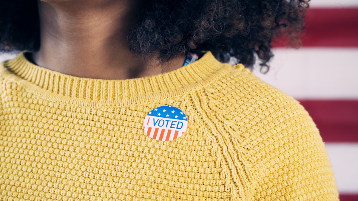 Young Gen Z Voter Wearing Sticker After Voting in Election
