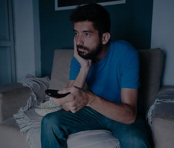 A man with prominent facial hair can be seen watching TV with a bored expression. His hand is cupping his cheek while the other hand holds a remote control. His shirt is blue.