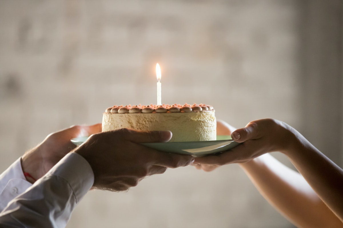 Close up of worker congratulate colleague with birthday, presenting baked cake with lit candle, employee greeting coworker, giving holding cream pie, celebrating, throwing party in office