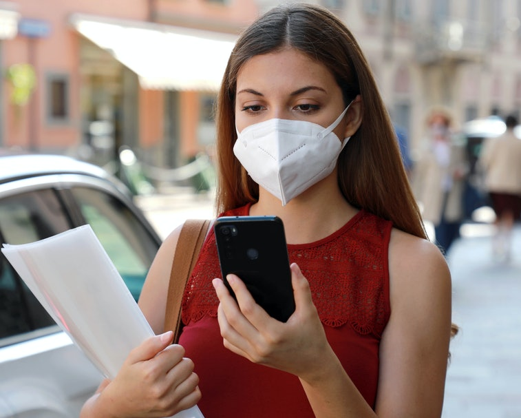 A young woman wearing a face mask is seen holding a smartphone in one hand and papers in her other arm. She is wearing a deep red sleeveless blouse, standing on a street near a car.