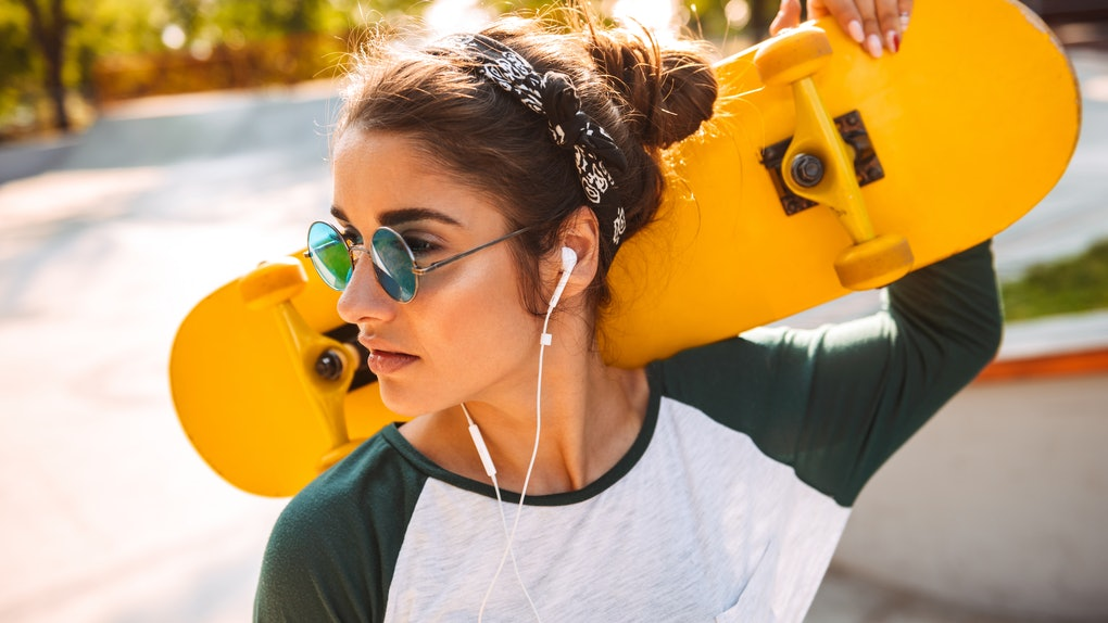 Photo of young beautiful woman walking outdoors with skateboard listening music with earphones.