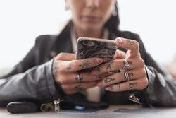 Young tattooed woman hands close up using smartphone.