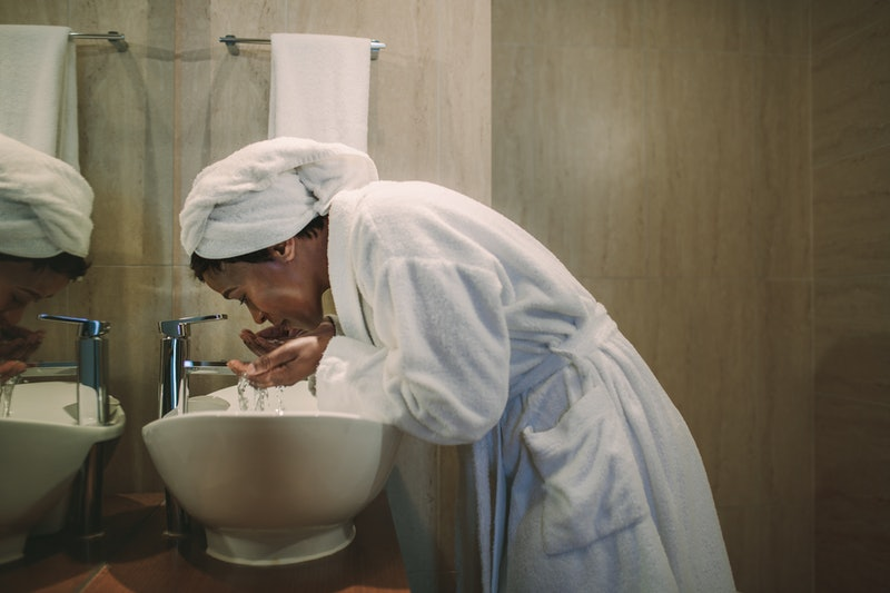 African woman in bathrobe washing her face in bathroom sink. Mature female washing her face in bathroom.