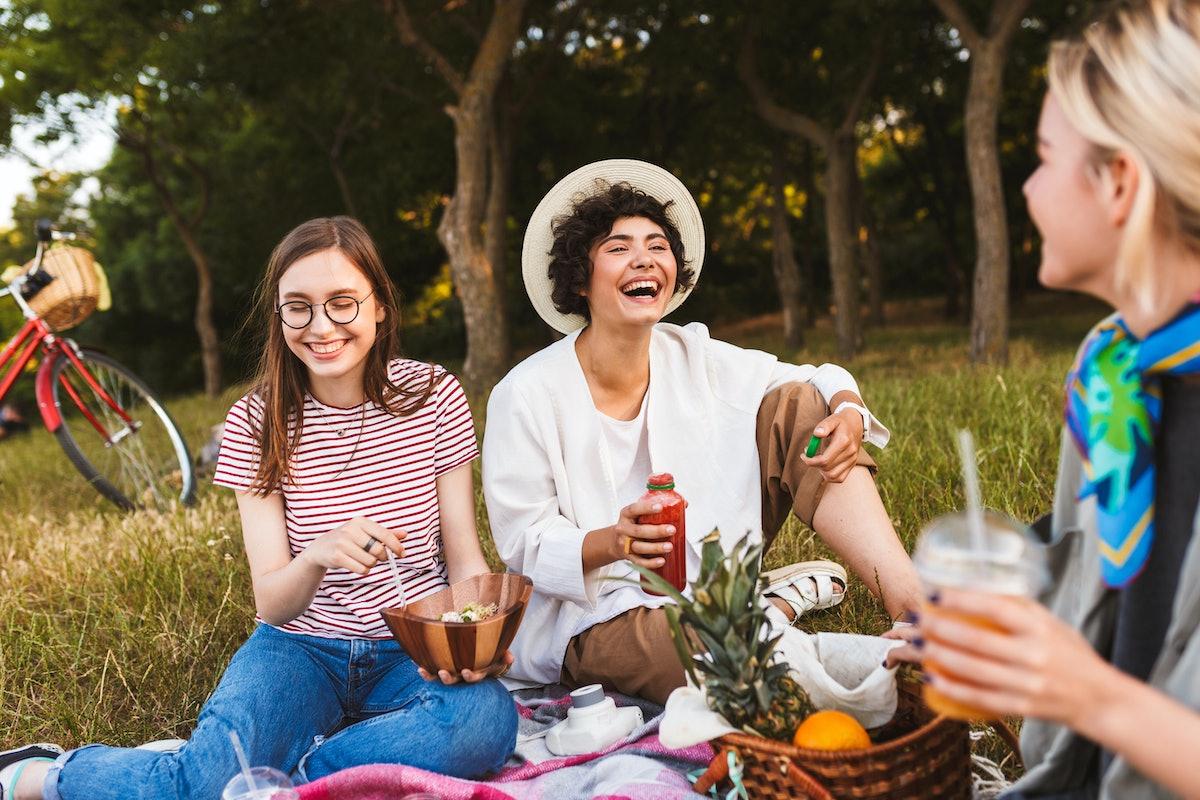 Smiling girls sitting on picnic blanket joyfully laughing spending time together on picnic in park
