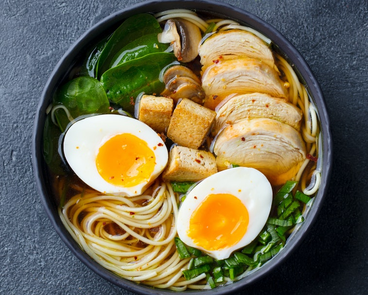 A black bowl of ramen with chicken, tofu, vegetables and egg.