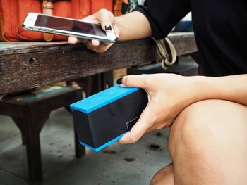 Woman using bluetooth speaker with smart phone