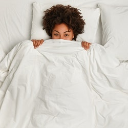 Cheerful black woman hides under soft white blanket, has fun in bed, rejoices good morning, has curly hair, rests in bed. View from above. Copy space. People, ethnicity and sleeping concept.