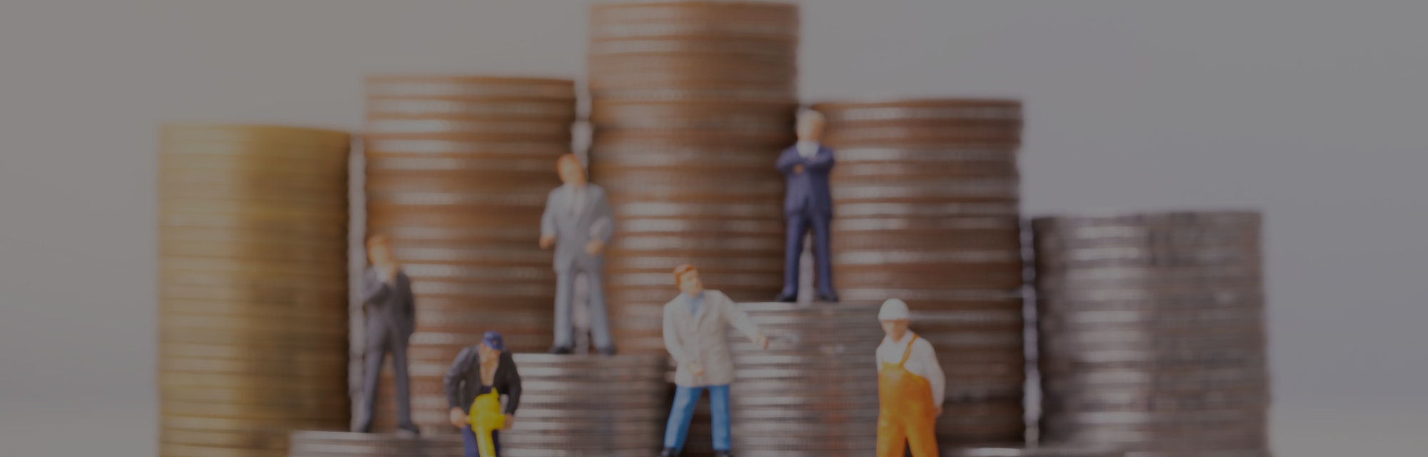 Miniature people standing on a pile of coins. Inequality and social class. Income and economic inequ...