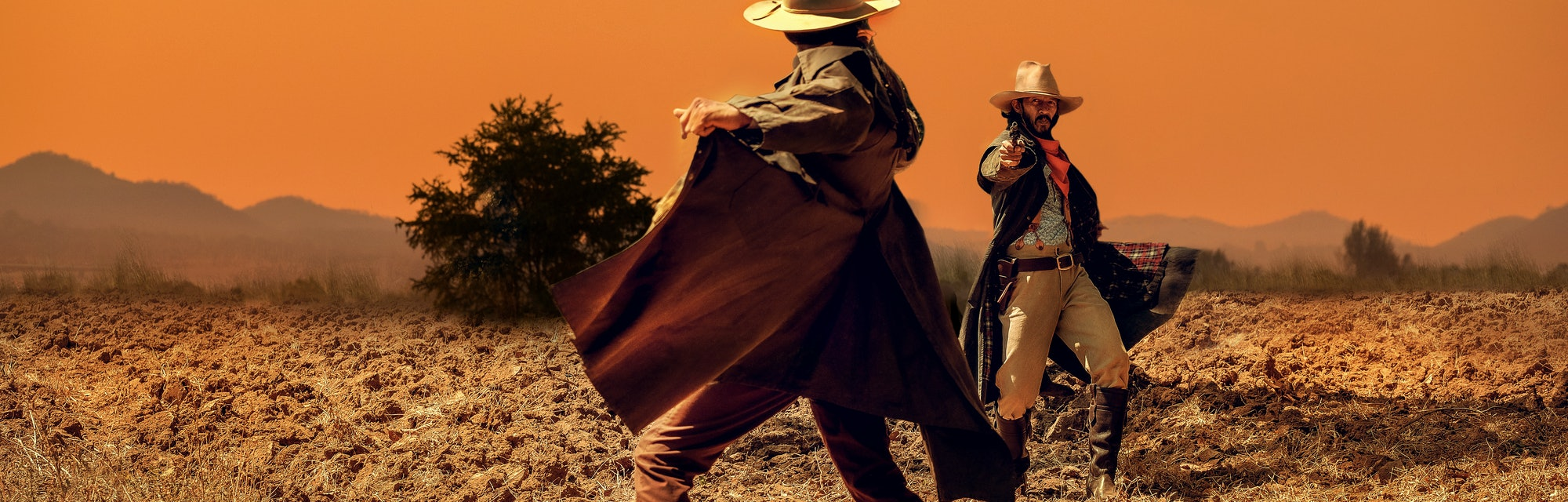 Cowboy Life: pistol shooting in a cowboy action shooting competition under sunset ,duel between cowboys. affair of honor